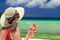 Young woman holding watermelon cocktail on the beach Stock Photo