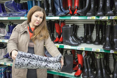 Young woman holding watertights when buying in shop Stock Photography