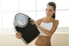 Young woman holding weight scale Stock Images