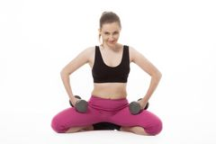 Young woman holding weights and doing fitness Royalty Free Stock Photo