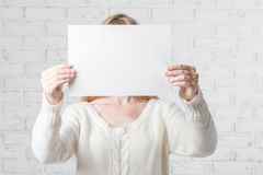 Young woman holding white banner with a place for your info Royalty Free Stock Images
