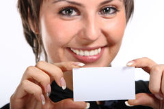 young woman holding a white card. Stock Photo