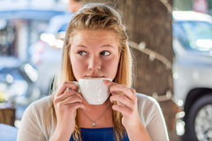 Young woman holding a white coffee cup sitting outdoors in a cafe Royalty Free Stock Images