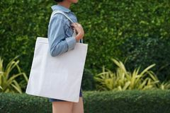 Free Young Woman Holding White Fabric Bag Walking In Park Stock Photography - 152017402