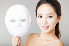 Young woman holding white mask Stock Photo