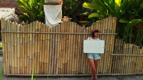 Young woman holding whiteboard with text travel. Travel concept, flying drone footage. Green background. Bali island. Young woman holding whiteboard with text stock video footage
