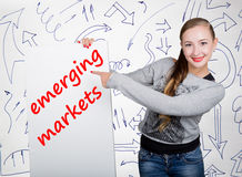 Young woman holding whiteboard with writing word: emerging markets. Technology, internet, business and marketing. Stock Photos