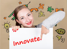 Young woman holding whiteboard with writing word: innovate. Technology, internet, business and marketing. Stock Image