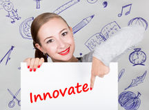 Young woman holding whiteboard with writing word: innovate. Technology, internet, business and marketing. Royalty Free Stock Photo