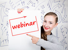 Young woman holding whiteboard with writing word: webinar. Technology, internet, business and marketing. Stock Photography