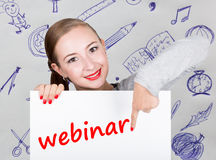 Young woman holding whiteboard with writing word: webinar. Technology, internet, business and marketing. Royalty Free Stock Photography