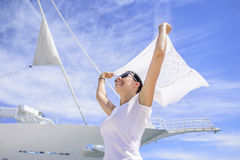 A young woman is holding a wind-scraped scarf in the wind against a white ship`s background. Royalty Free Stock Photography