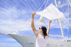 A young woman is holding a wind-scraped scarf in the wind against a white ship`s background. Stock Photo