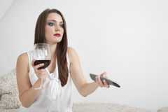 Young woman holding wineglass while changing channels with remote control Stock Photos