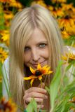 Young woman holding a yellow flower and smiling Stock Photos