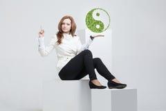 Young woman holding ying yang symbol Stock Photo