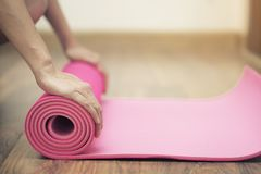 Young woman holding a yoga mat in exercise class Royalty Free Stock Photography