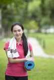 Young woman holding a yoga mat. In the garden Royalty Free Stock Photos