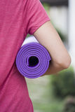 Young woman holding a yoga mat. In the outdoor Royalty Free Stock Photo