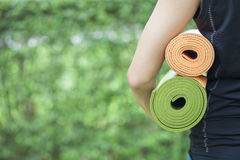 Young woman holding yoga mats Stock Images