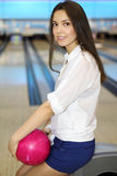 Young Woman Holds Ball And Sits In Bowling Club Stock Photography