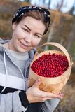 Young woman holding basket full of ripe red bilberries Royalty Free Stock Photos