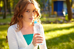 Young woman holds bottle of mineral water. Royalty Free Stock Images