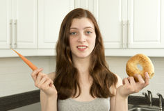 Young woman holds a carrot and a bagel Royalty Free Stock Images