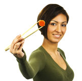 Young woman holds carrot slice with chopsticks Royalty Free Stock Photo