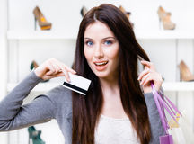 Young woman holds credit card in footwear shop Stock Photo