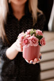 Young woman holds crimson cup with roses in hands. Concept of love, romantic gift and happiness, holidays and congratulations, St.Valentine`s day, Mother`s day Royalty Free Stock Images