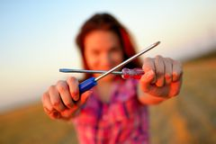 Young woman holds flat two screw in a hands at field Royalty Free Stock Image