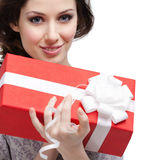 Young woman holds a gift. Wrapped in red paper, isolated on white Royalty Free Stock Image