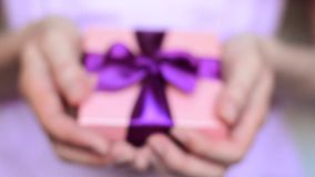 Young woman holds a gift box with a bow close up. Young woman holds a gift box with a purple bow close up