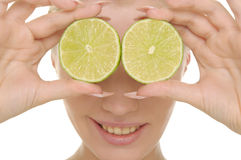 Young Woman Holds Halves Of Lime Before Eyes Royalty Free Stock Images