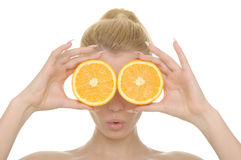 Young woman holds halves of oranges before eyes Royalty Free Stock Photos