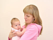 The young woman holds on hands of the baby. A family portrait Stock Photos