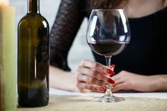 A young woman holds in her hand a glass of wine on a blind date. Close up stock photos