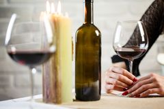 A young woman holds in her hand a glass of wine on a blind date. Two wineglass on the table. Close up royalty free stock photography