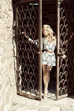 A young woman holds her hands behind the bars the door Stock Photo