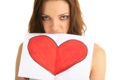 Young woman holds in her teeth painted heart Royalty Free Stock Photography