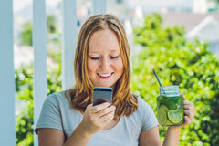 A young woman holds a mason jar in her hand with a mojito and a smartphone. Spring drink concept Royalty Free Stock Photography