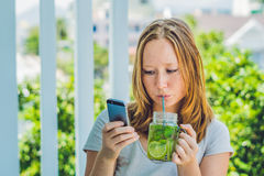 A young woman holds a mason jar in her hand with a mojito and a smartphone. Spring drink concept Stock Image
