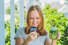 A young woman holds a mason jar in her hand with a mojito and a smartphone. Spring drink concept.  Stock Images