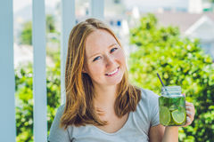 A young woman holds a mason jar in her hand with a mojito. Spring drink concept Royalty Free Stock Photo