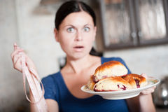 Young woman holds pie and a measuring tape Stock Photo