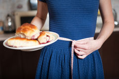 Young woman holds pie and a measuring tape Stock Images
