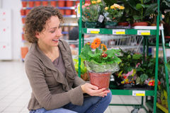 Young woman holds pot with flower Royalty Free Stock Image