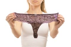 Young woman holds purple thong panties. On white background isolation Stock Photos