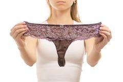 Young woman holds purple thong panties Stock Photos